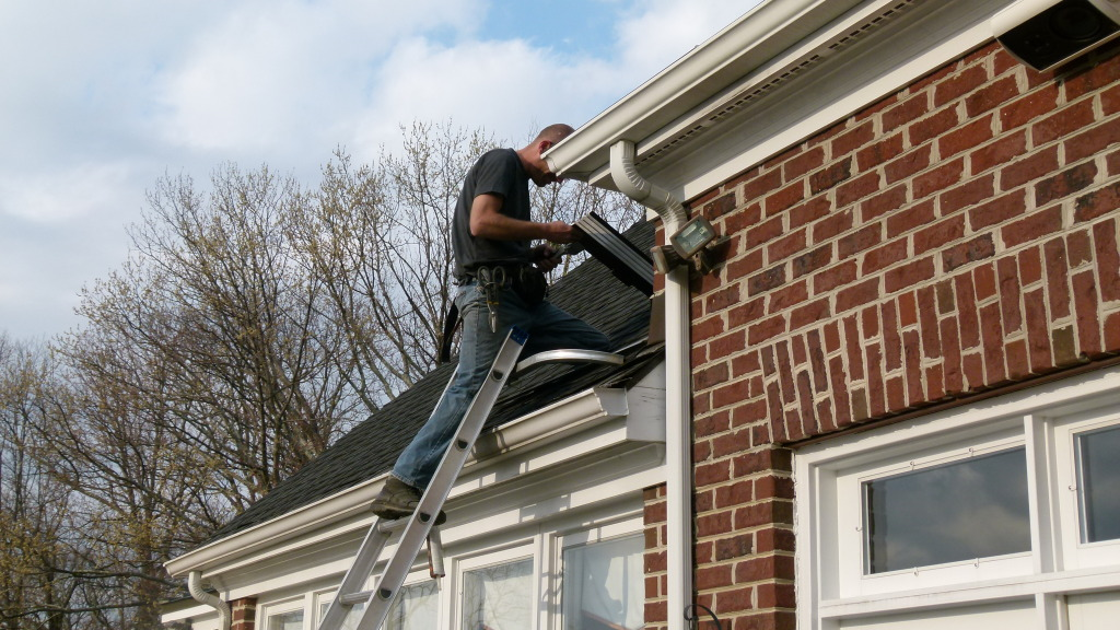 Professional installing gutter guards on home
